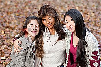 Hispanic mother and daughters hugging outdoors