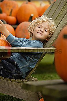 Boy in chair holding pumpkin
