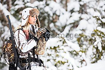 Caucasian woman hunting in forest with binoculars