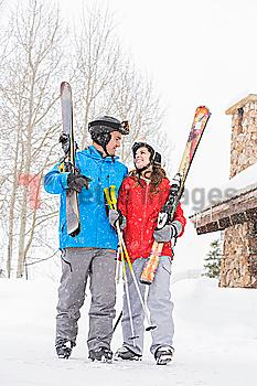 Smiling Caucasian couple carrying skis