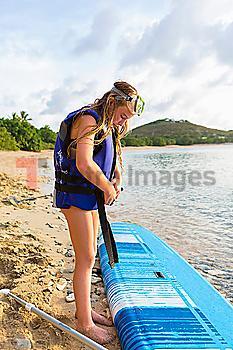Caucasian girl fastening life jacket near paddleboard