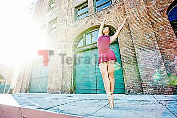 Sunbeams on mixed race woman dancing in city