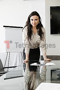 Mixed race businesswoman leaning over conference table
