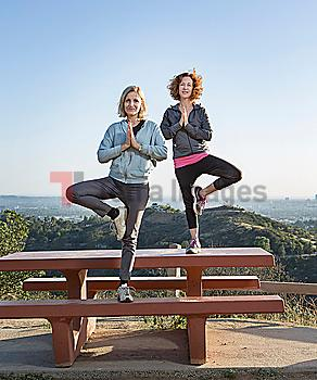 Caucasian women practicing yoga on hilltop