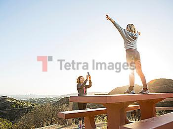 Caucasian woman photographing friend on hilltop
