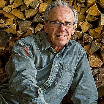 Caucasian man leaning on woodpile