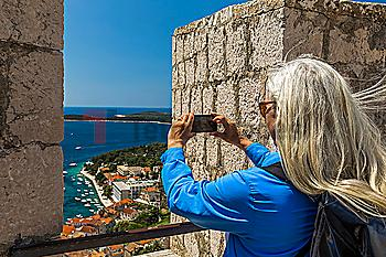 Caucasian woman photographing scenic view of ocean