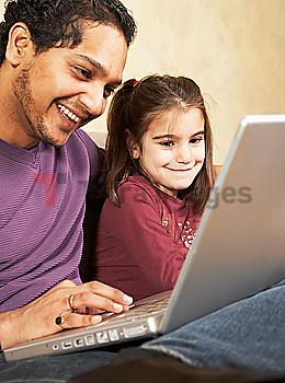 Indian father and daughter looking at laptop