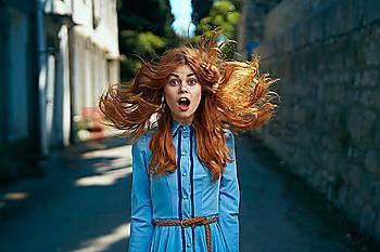 Wind blowing hair of surprised Caucasian woman