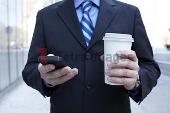 Businessman with smartphone and plastic cup