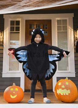 Young Chinese girl in butterfly costume with Halloween pumpkins
