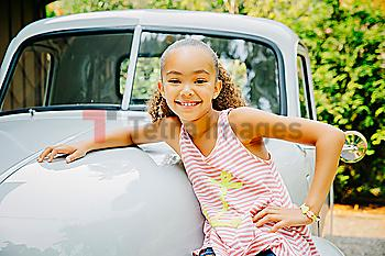 Mixed race girl leaning on car