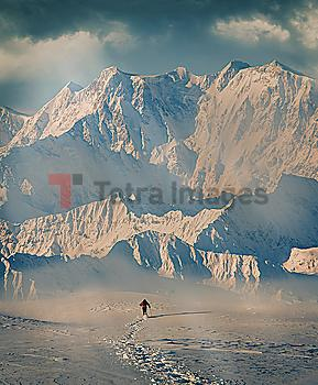 Man hiking through snow by mountain in Alpe Devero, Italy