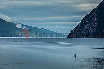 Man paddleboarding on Lake Garda, Italy