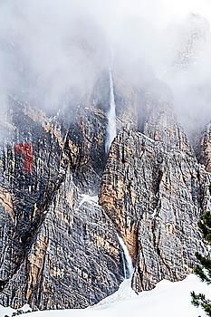 Snow falling down cliff in Dolomites, Italy