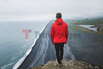 Man wearing red coat above beach in Vik, Iceland