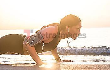 Woman wearing headphones doing push-up on beach