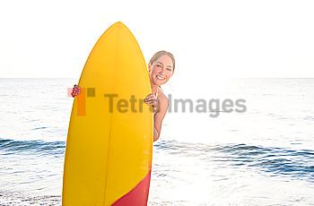 Smiling woman peering around surfboard on beach