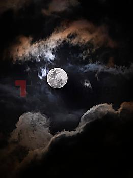 Full moon among clouds