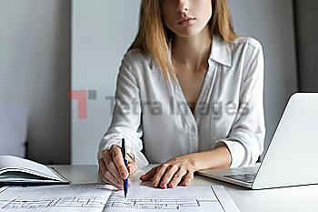 Young businesswoman working on blueprints