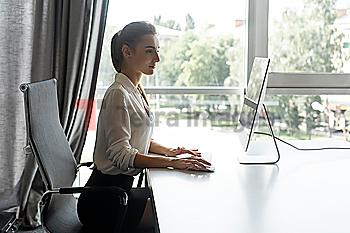 Young businesswoman working on desktop computer