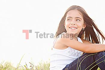 Wind blowing hair of Mixed Race girl sitting in grass