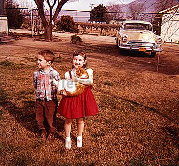 Caucasian brother and sister standing in yard holding cat