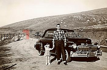 Portrait of Caucasian father and daughter posing near vintage car