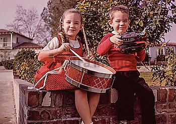 Caucasian brother and sister sitting on brick wall with toys
