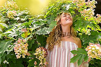 Smiling young woman among flowers