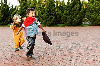 Boys playing in costumes on sidewalk
