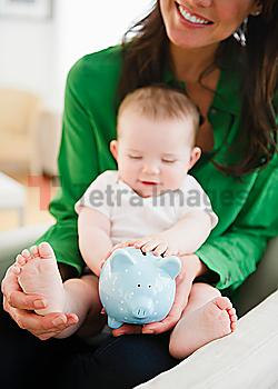 Mother holding baby daughter (6-11 months) and piggy bank
