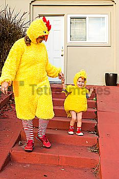 Caucasian mother and daughter wearing chicken costumes