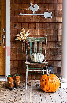 Pumpkins and corn on porch with boots in autumn