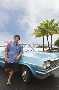 Asian man leaning on car