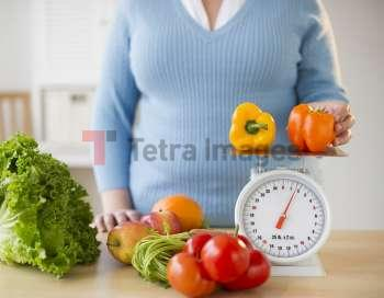 Overweight woman measuring peppers on a food scale