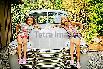 Mixed race sisters sitting on vintage car