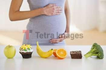 Pregnant woman standing behind a row of food