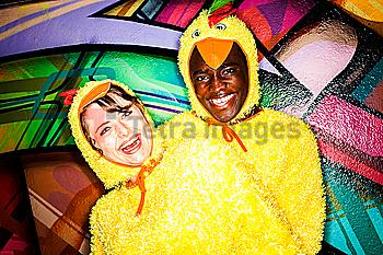 Couple in chicken costumes smiling near graffiti wall