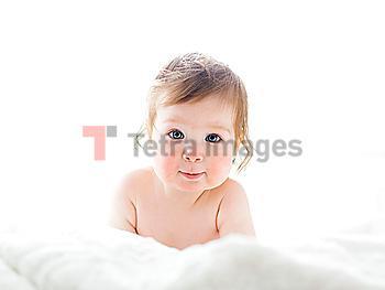 Baby girl lying on white sheet