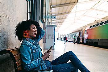 Young woman holding smart phone on railway platform