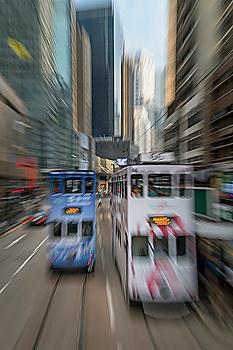 Blurred image of double-decker trams on street in Hong Kong, China