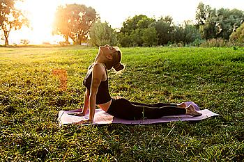 Young woman practicing yoga in park at sunset