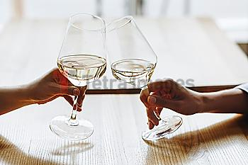 Hands of women toasting with glasses of white wine