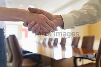 Close-up of business man and woman shaking hands