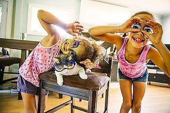 Mixed race sisters playing with face paint and googly eyes