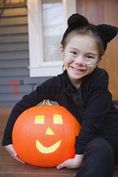 Mixed race young girl in cat costume holding Halloween pumpkin
