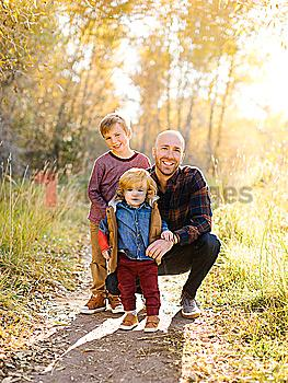 Smiling man with his sons on forest trail