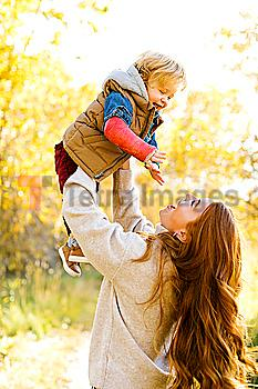 Smiling woman holding her son aloft in forest