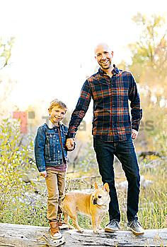 Father and son with pet French bulldog on fallen tree